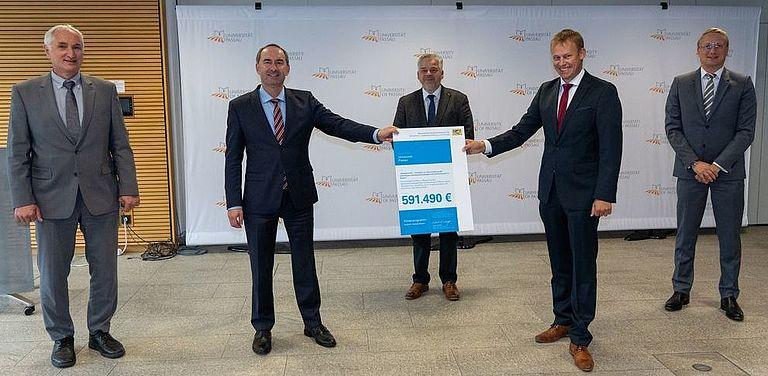 Bildhinweis: Staatsminister Hubert Aiwanger übergab den Förderbescheid an Präsident Prof. Dr. Ulrich Bartosch (links), Kanzler Dr. Achim Dilling (Mitte), Dr. Stefan Mang (2.v.r.) und Prof. Dr. Dirk Totzek (rechts). Foto: StMWi/E. Neureuther