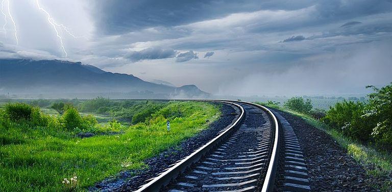Schienen verlaufen durch eine wettergebeutelte Landschaft.