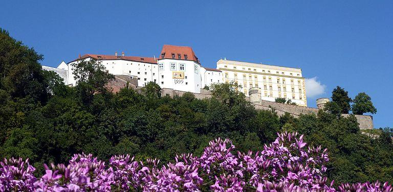 Foto von der Veste Oberhaus mit Blumen im Vordergrund.