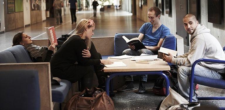Studierende der Rechtswissenschaften lernen zusammen in Gang einer Universität.