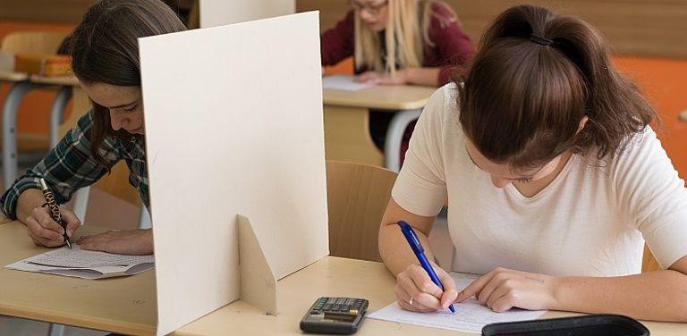 Schüler:innen im Klassenzimmer schreiben eine Prüfung.