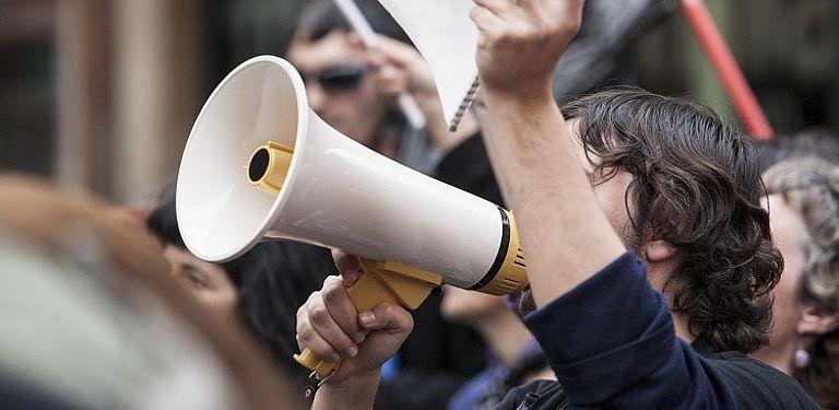 Bild von einer Person mit Megafon zum Projekt NGOs Firms von Prof. Dr. Krautheim; Bild: Adobe Stock