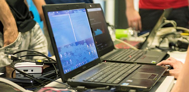 Menschen stehen um einen Tisch mit Laptops und vielen Kabeln.